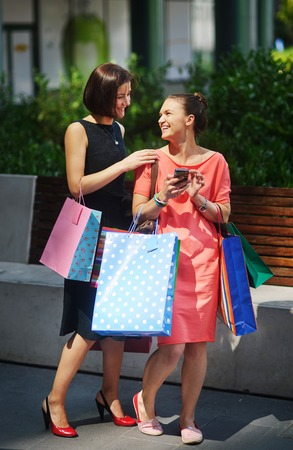 Two lovely young women have visited shopping center. They are very happy. In the hands of girlfriends a lot of bright multi-colored packages. They have something to discuss.