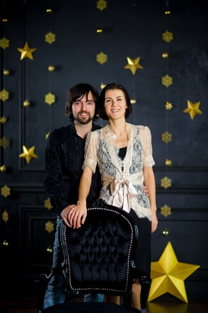 Nice young couple stands against the background of festively decorated dark wall. Young man gently embraces the girlfriend. Woman is elegantly dressed. Young people with a smile look in the camera.