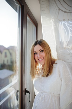 Charming pregnant woman in beautiful dress stands near a window with white curtains. On a woman's face a happy smile.