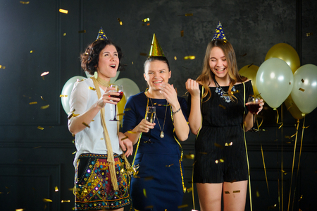 Three young women celebrate something. In hands at everyone a glass with champagne. They are elegantly dressed. From above on girlfriends the gold confetti falls. The room is decorated with balloons.