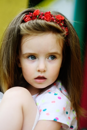 Portrait of the charming girl of 4-5 years. Beautiful long fair hair. A wreath from red colors on the head. Expressive gray-blue eyes. Bright lips.