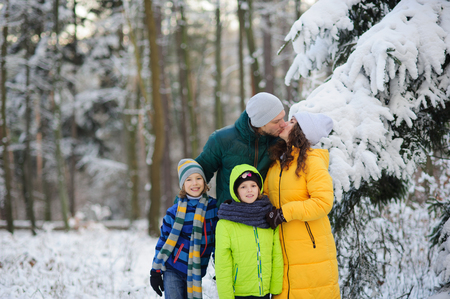 Family portrait in the winter forest. Happy family against the background of snow-covered trees.