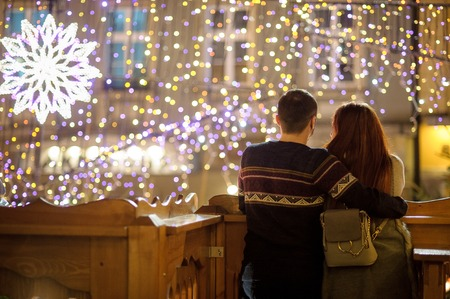 Young couple admires a view of the festive city. Young people stand having embraced. Rear view.