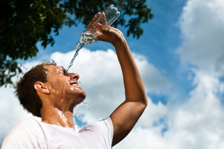 sportsman throwing water over his head for refreshment