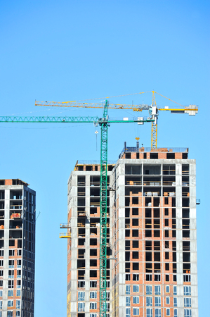 Crane and building under construction against blue sky