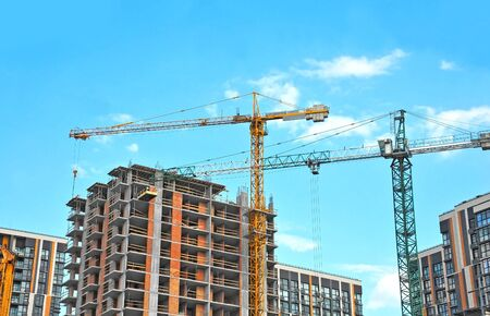 Photo pour Crane and building under construction against blue sky - image libre de droit