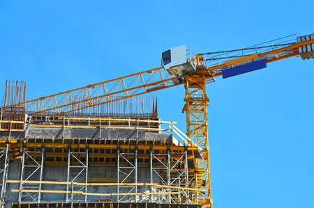 Photo pour Crane and building under construction against blue sky - image libre de droit