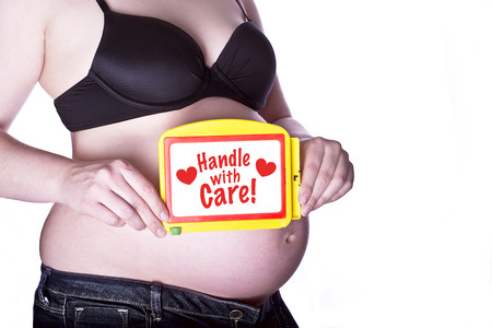 "pregnant woman clothed in black bra and jeans holding a toy slate with text ""handle with care"" in front of her bellyの写真素材"