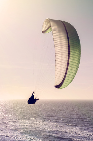 silhouette of a paraglider over the ocean in the evening sun