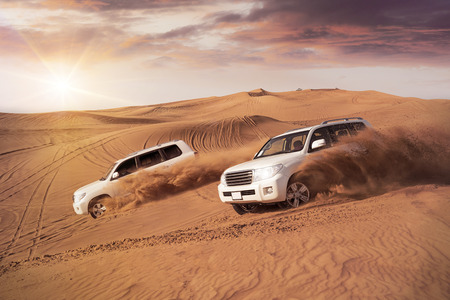 Photo pour two 4x4 vehicles bashing side to side through the desert dunes in the evening sun - image libre de droit
