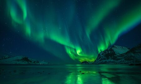 Photo for wonderful night sky with aurora borealis over a beach with reflections, lofoten, norway - Royalty Free Image