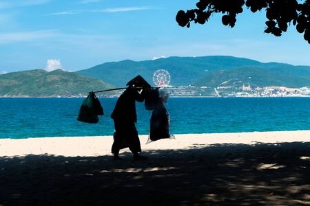 Photo pour Silhouette of food delivery man on beach in asian hat and an amusement park on background - image libre de droit