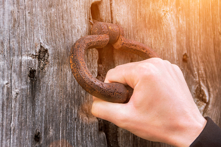 Photo for Old bell at the door, hand knocks on the wooden door - Royalty Free Image