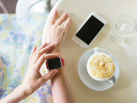 Youth and technology. Womans hands with smartwatch, smartphone, coffee and glass of water on the table. Focus on smartwatch.