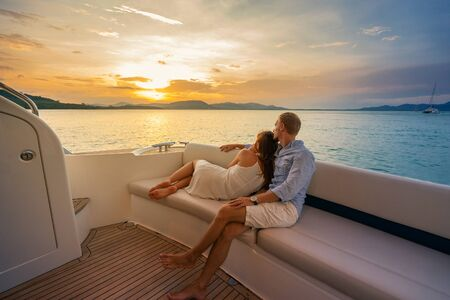 Photo pour Romantic vacation . Beautiful couple looking in sunset from the yacht. - image libre de droit