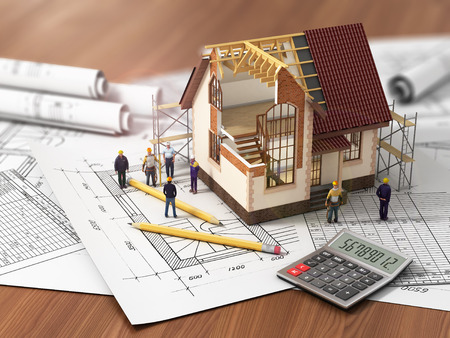 House with open interior on top of blueprints documents and mortgage calculations and builders