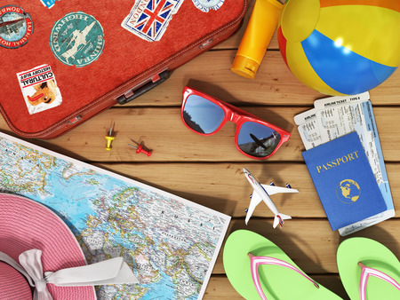 Travel concept. Snglasses, world map, beach shoes, sunscreen, passport, planeickets, beach ball, hat and old red suitcase for travel on the wood background.