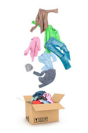 Photo pour Clothes Falling Into The Cardboard Box Isolated On White - image libre de droit