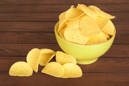 tasty potato chips in green bowl on wooden table