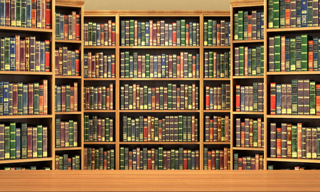 Foto de Table on background of bookshelf full of books . Old library. - Imagen libre de derechos