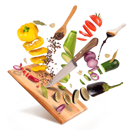 Photo pour Flying slices of sliced vegetables are served on a wooden board on a white background. - image libre de droit