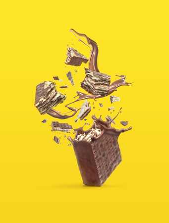 Wafers are broken into pieces, with a chocolate splash isolated on a bright background