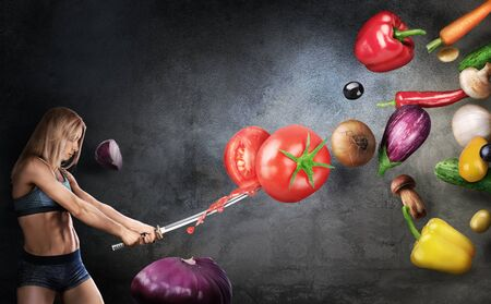 Foto de Healthy eating concept. Young fitness girl cuts flying vegetables with a Japanese sword on a dark background. Cooking concept. - Imagen libre de derechos
