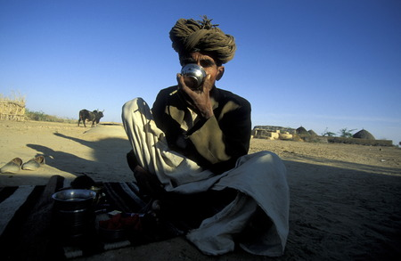 a men drinks water in the deset of tar near the town of Barmer in the province Rajasthan in India.