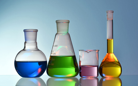 Photo for Laboratory glassware with colorful liquids and chemicals on blue background - Royalty Free Image