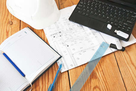 Photo pour helmet, notebook, drawing tools on wooden plate - image libre de droit