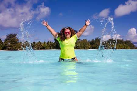 Photo pour A slender woman with curly hair in a wet bright T-shirt in the turquoise water of the Lagoon on the Bora Bora island in French Polynesia - image libre de droit