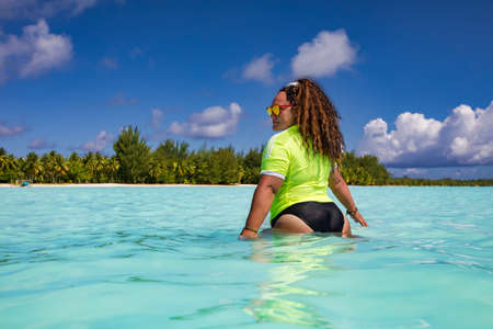 Photo pour A slender woman with curly hair in a wet bright T-shirt in the turquoise water of the Blue Lagoon on the Bora Bora island in French Polynesia - image libre de droit