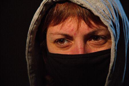 Photo pour Portrait of a young woman in a black balaclava. - image libre de droit