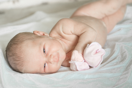 Foto de Closeup portrait of cute newborn baby lying down in the bed at home, smiling face, happy childhood, new life concept - Imagen libre de derechos