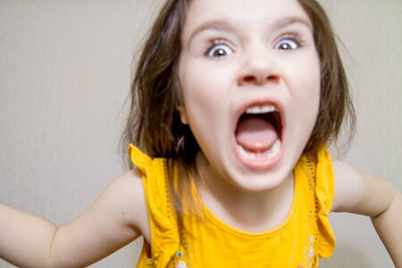 Photo pour defocused funny close up portrait of a Little agressive angry girl screaming on white background - image libre de droit