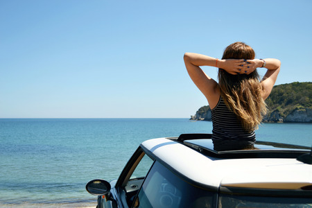 Rear view of relaxed woman on summer travel vacation to the coast towards the sea leaning out the car sunroof.