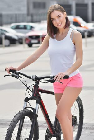 Photo pour Portrait young beautiful smiling girl wearing a white t-shirt and pink short rides a bicycle through the streets of the city - image libre de droit