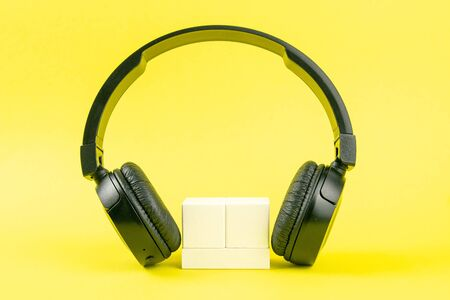 Photo pour Black headphones and wooden cubes on a yellow background. On cubes you can enter your date, month and day. - image libre de droit