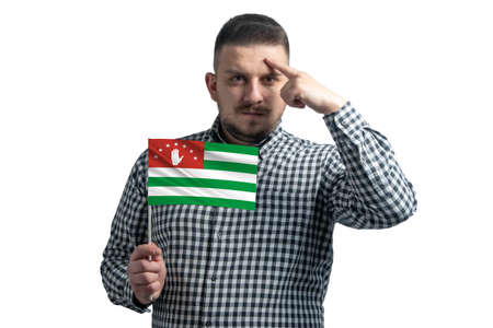 Photo pour White guy holding a flag of Abkhazia and a finger touches the temple on the head isolated on a white background. - image libre de droit