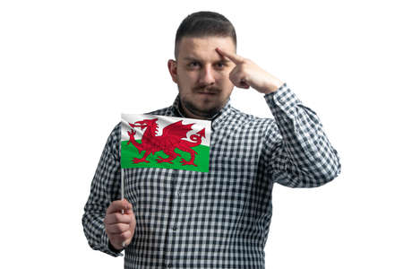 Photo pour White guy holding a flag of Wales and a finger touches the temple on the head isolated on a white background. - image libre de droit