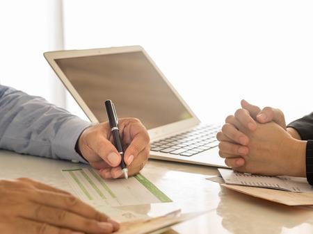 Photo pour Businessman is writing a deposit slip. - image libre de droit