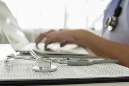 Foto de Close-up of a doctor typing on keybord in the office - Imagen libre de derechos