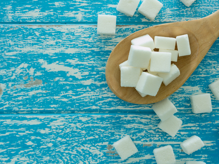 cube sugar on wooden spoon and  sugar on wooden background