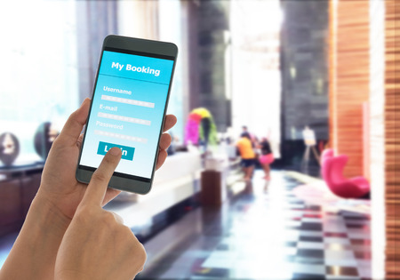 Photo pour close-up view of holding mobile smart phone Booking hotel. - image libre de droit