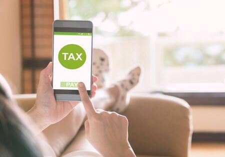 Photo pour Filing taxes online using smartphones and the internet on mobile. - image libre de droit