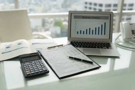 Photo for Workplace. The pen on balance sheet report with calculator, laptop computer showing business graph for analysis performance of operation. - Royalty Free Image