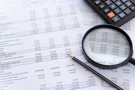 Photo for accounting audit concept. calculator and magnifying glass on financial statement and balance sheet annual on auditor's desk. - Royalty Free Image