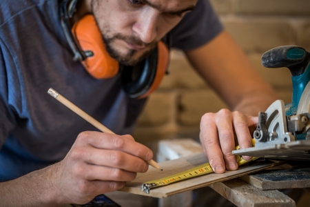 the man makes the measurements on the Board to work with manual electric saw ,close-up , concept building and repair