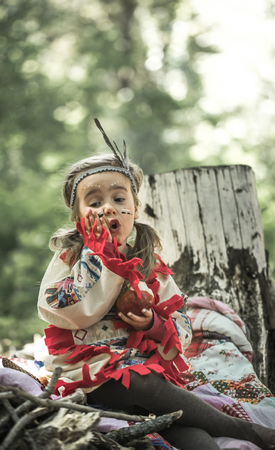 little cute girl in costume of American Indian ,plays near a tree and eating an Apple ,the concept of children and childhood