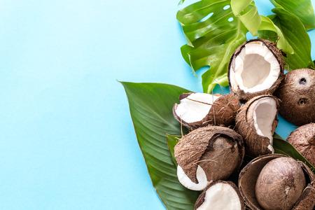 Photo pour Fresh coconut halves with tropical leaves on blue background. Flat - image libre de droit